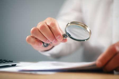 Foto de Businessman reading documents with magnifying glass concept for analyzing a finance agreement or legal contract - Imagen libre de derechos