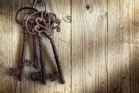 Foto de Old skeleton keys hanging against a wooden background - Imagen libre de derechos