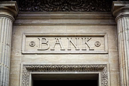 Photo pour Old bank sign engraved in stone or concrete above the door of financial building concept for finance and business - image libre de droit