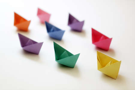 Photo pour Paper boats of multi-colour following a leader boat concept for leadership, teamwork and winning success - image libre de droit