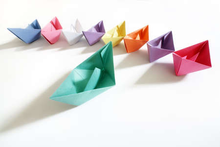 Photo for Paper boats of multi-colour following a leader boat concept for leadership, teamwork and winning success - Royalty Free Image