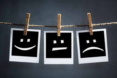 Photo for Happy, sad and neutral emoticons on instant print transfer photographs hanging on a clothesline - Royalty Free Image