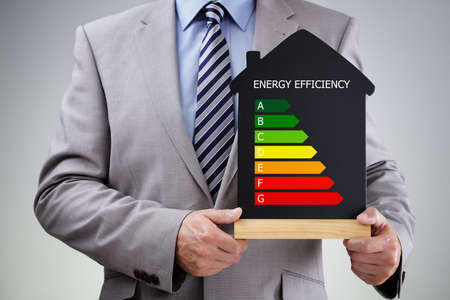 Foto de Businessman holding house shape blackboard with chalk energy efficiency rating chart concept for performance, efficiency and environmental conservation - Imagen libre de derechos