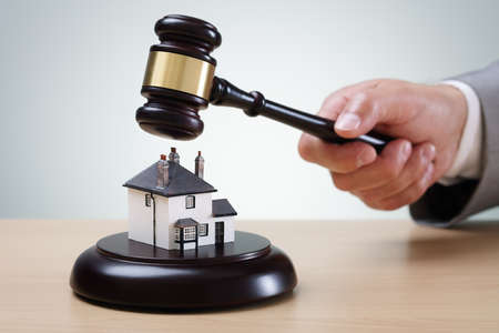 Photo pour Bidding on a home, gavel and house concept for home ownership, buying, selling or foreclosure - image libre de droit