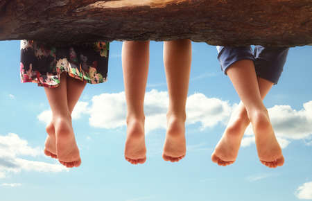 Photo pour Three kids sitting in a tree dangling their feet against a blue sky in summer concept for family, friends, carefree and vacations - image libre de droit