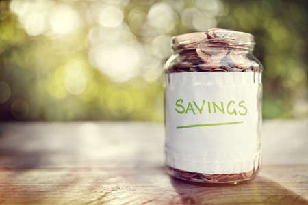 Foto de Savings money jar full of coins concept for saving or investment for a house, retirement or education - Imagen libre de derechos