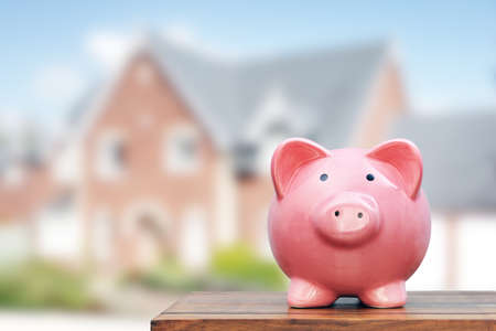 Photo for Saving to buy a house, real estate or home savings, piggy bank in front of property - Royalty Free Image