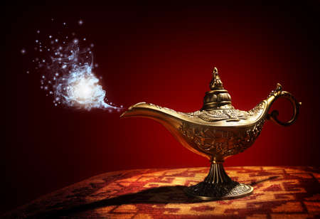 Foto de Magic lamp from the story of Aladdin with Genie appearing in blue smoke concept for wishing, luck and magic - Imagen libre de derechos