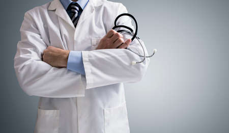 Photo for Doctor holding a stethoscope with arms crossed and copy space - Royalty Free Image