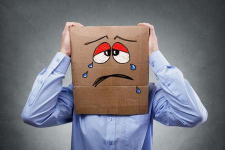 Foto de Businessman with cardboard box on his head showing a crying sad expression concept for headache, depression, sadness, heartache or frustration - Imagen libre de derechos