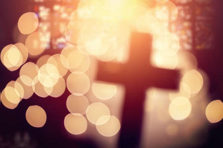 Photo pour Abstract defocussed cross silhouette in church interior against stained glass window concept for religion and  prayer - image libre de droit
