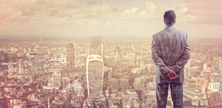 Photo pour Businessman looking across the city of London financial district concept for entrepreneur, leadership and success - image libre de droit
