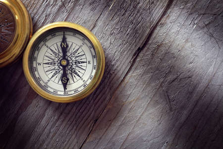 Photo pour Antique golden compass on wood background concept for direction, travel, guidance or assistance - image libre de droit