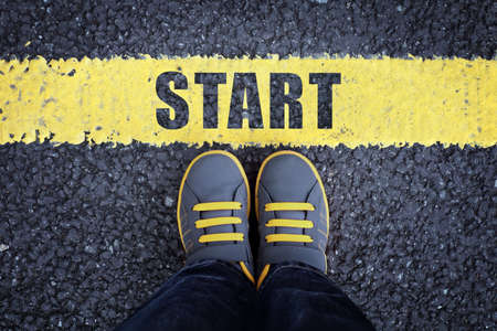 Photo pour Start line child in sneakers standing next to a yellow starting line - image libre de droit