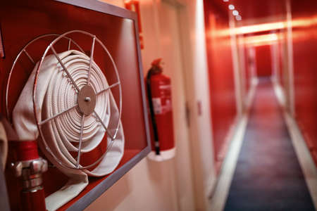 Photo pour Fire extinguisher and fire hose reel in hotel corridor - image libre de droit