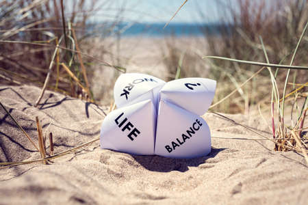 Photo pour Origami fortune teller on vacation at the beach concept for work life balance choices - image libre de droit