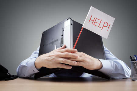 Photo pour Frustrated and overworked businessman burying his head uner a laptop computer asking for help - image libre de droit