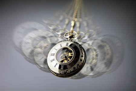 Foto de Hypnotism concept, gold pocket watch swinging used in hypnosis treatment - Imagen libre de derechos