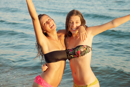 Happy girls with long hair feeling air sitting on sand