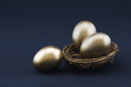 Photo for Black background adds drama to success concept of three, gleaming gold nest eggs.  Copy space available on horizontal photograph.  - Royalty Free Image
