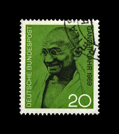 Foto de Mahatma Gandhi (1869-1948) aka Mohandas Karamchand Gandhi, famous indian activist, indian independence movement leader against British rule, circa 1969. vintage canceled post stamp printed in Germany isolated on black background. - Imagen libre de derechos