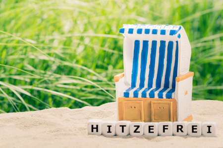 Foto de Too hot to work concept. Dice form the German word Hitzefrei (too hot to work in English) next to a beach chair and a parasol. - Imagen libre de derechos