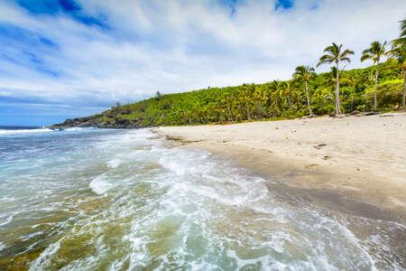 Foto de Sunny day with rocks, waves and sand at Grande Anse Beach, Reunion Island - Imagen libre de derechos