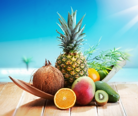 Foto de Fresh Fruits on the beach at a deck in front of an island with a palm. Assorted tropical fruits, orange,Ananas or pineapple, lime,mango and avocado. - Imagen libre de derechos