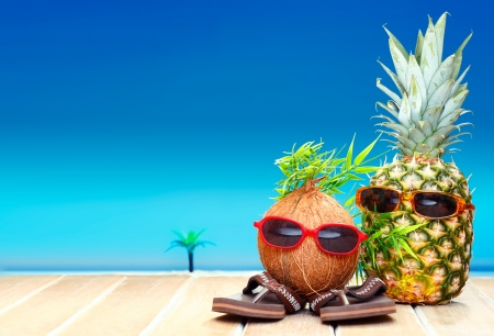 Photo pour Two fruity friends, a coconut and pineapple, with fun foliage haistyles and trendy sunglasses in tropical paradise - image libre de droit