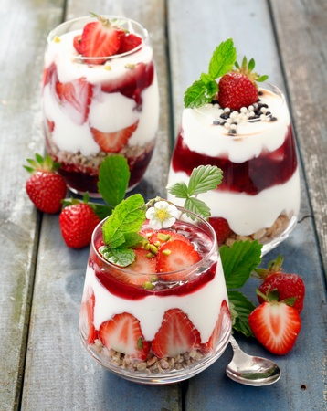 Assortment of creamy gourmet strawberry desserts layered in decorative patterns in individual glass containers