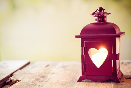 Foto de Decorative red metal lantern with a heart cutout lit by a glowing candle with copyspace for Valentines or Christmas - Imagen libre de derechos