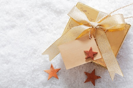 Photo for Decorative gold Christmas gift in winter snow with a blank label for your seasonal greeting and a scattering of small stars - Royalty Free Image