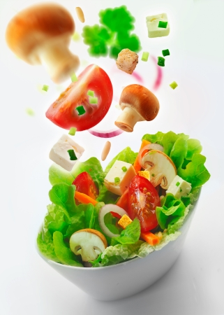 Individual side bowl of healthy fresh mixed green salad of lettuce, carrot, onion, mushrooms, tomato and feta with additional ingredients in th air receding into the distance on a white background