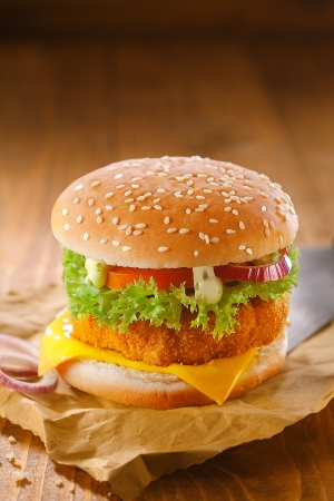 Photo pour Delicious chicken burger with a golden crumbed patty and salad ingredients on grungy crumpled brown paper against a wooden backdrop with copyspace - image libre de droit
