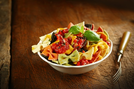 Multicoloured Italian bow tie pasta topped with tomato and garnished with basil served in a white ceramic bowl with a fork on an old wooden table