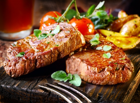 Foto de Succulent thick juicy portions of grilled fillet steak served with tomatoes and roast vegetables on an old wooden board - Imagen libre de derechos