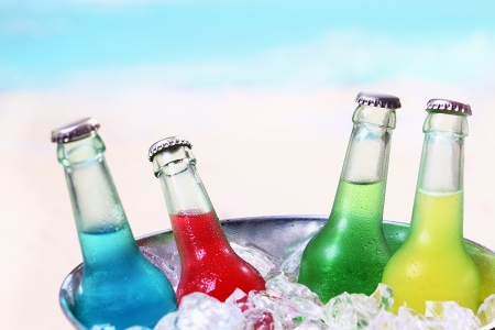 Foto de Colourful chilled soda drinks in unlabeled glass bottles standing in a metal container of crushed ice cubes for a summer party - Imagen libre de derechos
