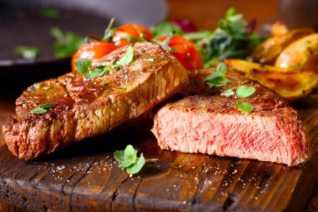 Photo pour Delicious portion of healthy grilled lean medium rare beef steak cut through and served on a wooden kitchen board garnished with fresh herbs - image libre de droit