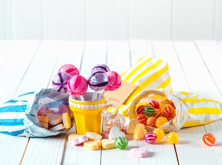 Photo for Assortment of many candy types with marshmallows and lollipops in bags and cup laid over a white wooden table - Royalty Free Image