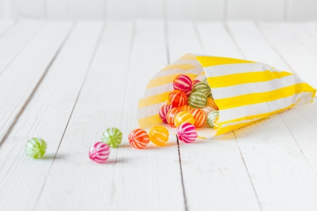 Photo for Yellow striped candy bag spilling its candies over a white wooden table - Royalty Free Image