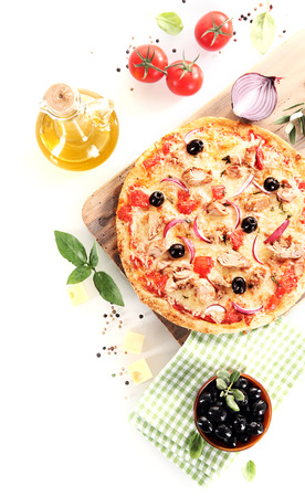 Foto de Top view of a tuna, olives, onion and basil pizza over a wooden board surrounded by the ingredients - Imagen libre de derechos