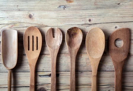 Row of assorted old wooden kitchen utensils lying on a grungy cracked wooden surface in a country kitchen