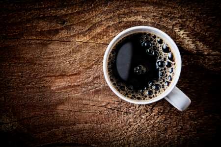 Foto de Close up overhead view of a cup of strong frothy espresso coffee on a rough textured wooden surface with dark vignetting and a highlight around the mug, with copyspace - Imagen libre de derechos