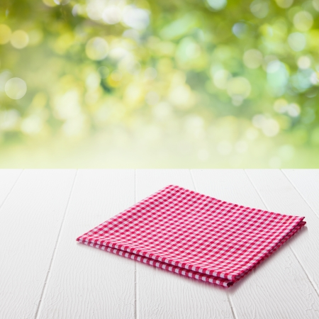 Neatly folded fresh red and white checked cloth conceptual of a country or rustic ambiance on a garden table in a sunny summer garden with focus to the napkin