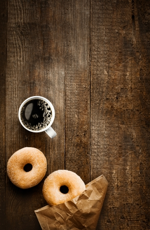Foto de Overhead view of two tempting fresh sugared doughnuts with their brown paper wrapping and a cup of strong black filter or espresso coffee on a rustic wood table - Imagen libre de derechos