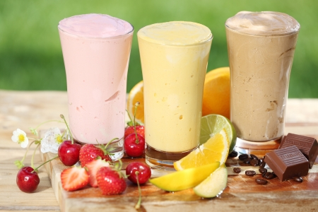 Photo for Three delicious smoothies with yoghurt or ice cream blend, two made with fruit and one of chocolate, together with various fresh tropical fruit on a garden table - Royalty Free Image