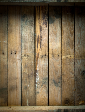 Foto de Background texture of a grungy stained and weathered wooden table top with a line of old nails and parallel vertical planks - Imagen libre de derechos