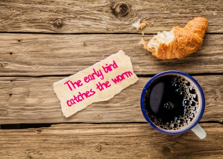 Photo pour The early bird catches the worm, an inspirational saying hand written on a small torn piece of paper alongside an early breakfast of frothy espresso coffee and a half devoured fresh golden croissant - image libre de droit