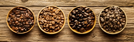 Foto de Selection of four different fresh dried roasted coffee beans in individual containers arranged in a line viewed from above on a textured driftwood background - Imagen libre de derechos