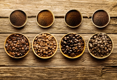 Foto de Preparing fresh roast coffee beans to brew with an overhead view of four different varieties of beans with their corresponding ground powder in small dishes on a weathered driftwood background - Imagen libre de derechos